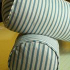 Feather bolsters with piped covers in blue and white ticking