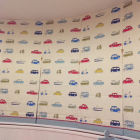 5 children's blinds with red ric rac and gingham edge on a curved bay